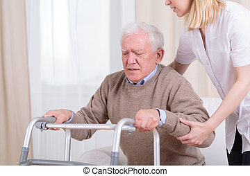 Helping to stand up - Careful nurse helping senior man with...