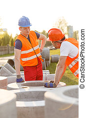 Small talk at work - Tired construction workers having small...