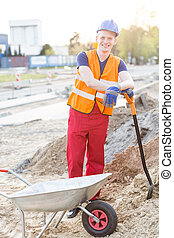 Worker with shovel - Young happy construction worker leaning...