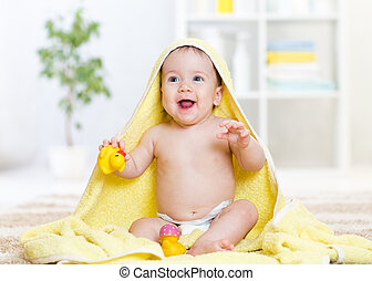 Adorable happy baby girl in towel at home