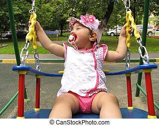Small child rides on the chain swing with pleasure