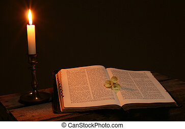 bible prayer book candle - bible on table by candle light....