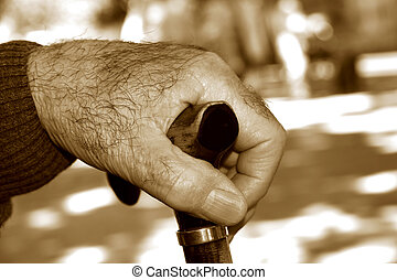 old man with a walking stick, in sepia toning - closeup of...