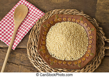 Millet - Peeled raw millet from organic farming on rustic...