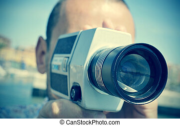 young man filming with a retro film camera - closeup of a...