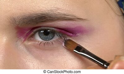 Eye make-up woman applying eyeshadow, making exotic, close...