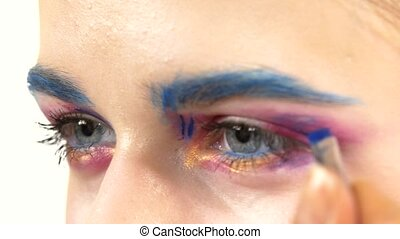 Eye make-up woman applying eyeshadow, making exotic, one, blue eyebrow, yellow shadow, mascara, finishing touch, close up, on white