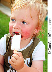 child eating ice cream. Messy small boy with blond hair...