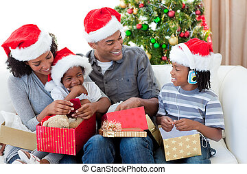 Happy Afro-American family opening Christmas presents at...