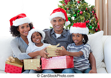 Smiling Afro-American family sharing Christmas presents on...