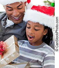 Portrait of a happy Afro-American father and son opening a Christmas gift
