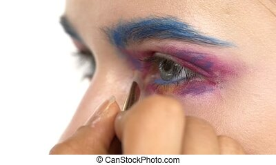 Eye make-up woman applying eyeshadow, making exotic, one, blue eyebrow, shadow, mascara, finishing touch, close up, on white, slow motion