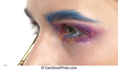 Eye make-up woman applying eyeshadow, making exotic, one, blue eyebrow, yellow shadow, mascara, finishing touch, close up, on white, slow motion