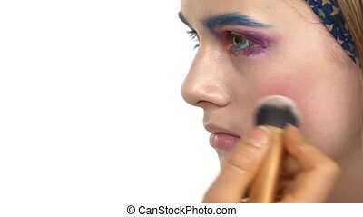 Eye make-up woman applying eyeshadow, making exotic, one, blue eyebrow, yellow shadow, blusher, mascara, finishing touch, close up, on white, slow motion