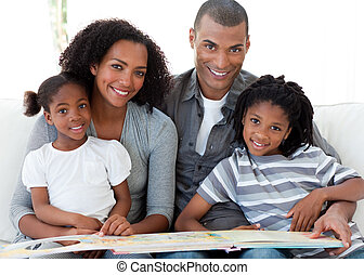 Portrait of a smiling Afro-American family reading a book in...