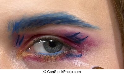 Make-up artist applying light paint on models eye, exotic...