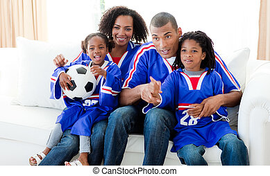 Afro-American family watching a football match at home -...