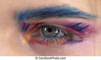 Eye down make-up woman applying eyeshadow, making exotic, one, blue eyebrow, yellow shadow, mascara, finishing touch with special brush, close up, on white, slow motion
