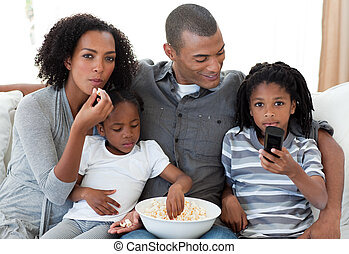 Afro-American family watching a film at home and earting...