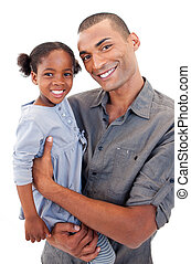 Happy Afro-American dad holding her little daughter agaisnt...