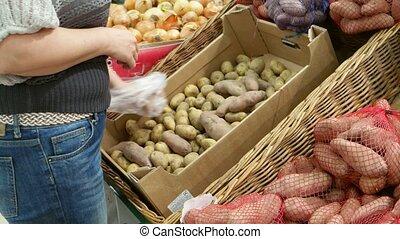 Woman chosing potato shopping in department store uhd...