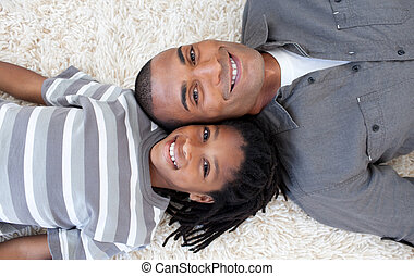 Afro-American father and son sleeping on the floor