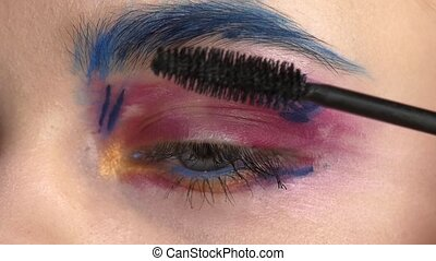 Eye down make-up woman applying eyeshadow, making exotic, one, blue eyebrow, yellow shadow, mascara, finishing touch, close up, on white, slow motion