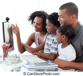 Afro-American family working with a computer at home -...