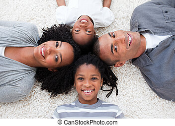 Smiling Afro-American young family lying on floor in a...