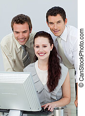 Smiling business people using a computer