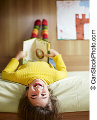 girl reading book - girl lying on bed and reading book