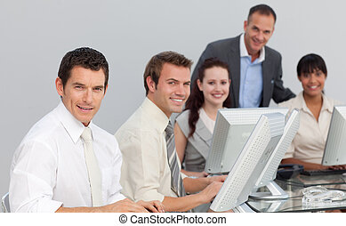 Multi-ethnic business team working with computers in an...