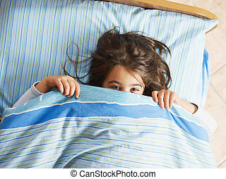 Shy girl - Girl under covers, looking at camera. High angle...