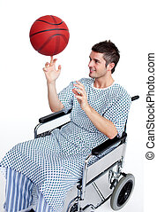Patient in wheelchair spinning a basket ball on his finger -...