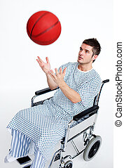 Patient in wheelchair having fun with a basket ball