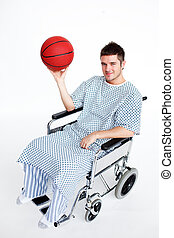 Patient in wheelchair holding a basket ball - Attractive...