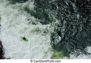 Green Kayak in White Water - A green kayaker paddles through...