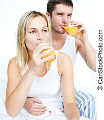 Couple drinking orange juice in bed - Happy couple drinking...