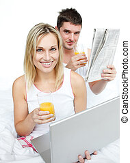 Couple drinking orange juice and reading news in bed - Happy...