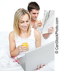 Couple reading a newspaper and using a laptop in bed -...