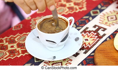 A person using a spoon to stir a coffee drink in Turkey - A...