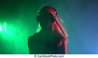 Sexy blonde dj girl playing and listening to music, smoke, silhouette