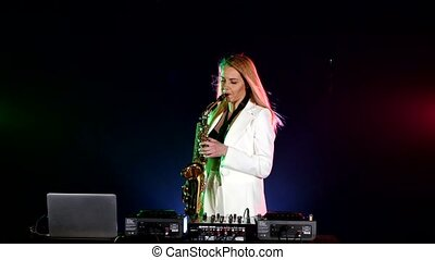 Young sexy, blonde woman dj playing music using saxophone on black