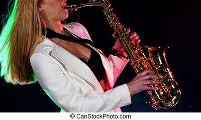 Young sexy, blonde woman dj in white jacket playing music using saxophone on black, cam moves upward