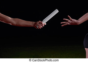 athletic runners passing baton in relay race - woman...