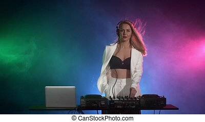 Beautiful, sexy dj girl in white jacket, headphones playing...