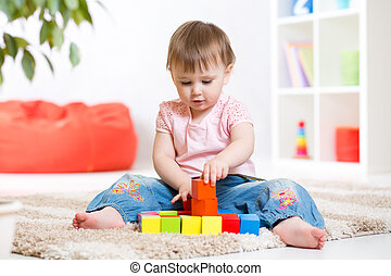 kid girl playing wooden block toys