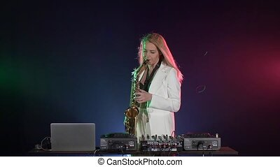 Young sexy, blonde woman dj playing music using saxophone on...