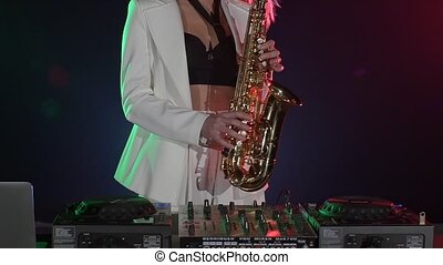 Young sexy, blonde woman dj in white jacket playing music using saxophone on black, cam moves upward, slow motion