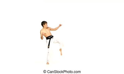 Karate or taekwondo man performs tricks Isolated on white -...